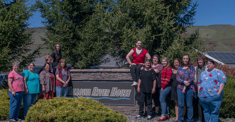 wallowa river house staff standing in front of the sign